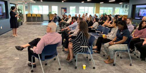 Doral Chamber of Commerce introduces DCC 21st Century Technology event, people listening to a third host.