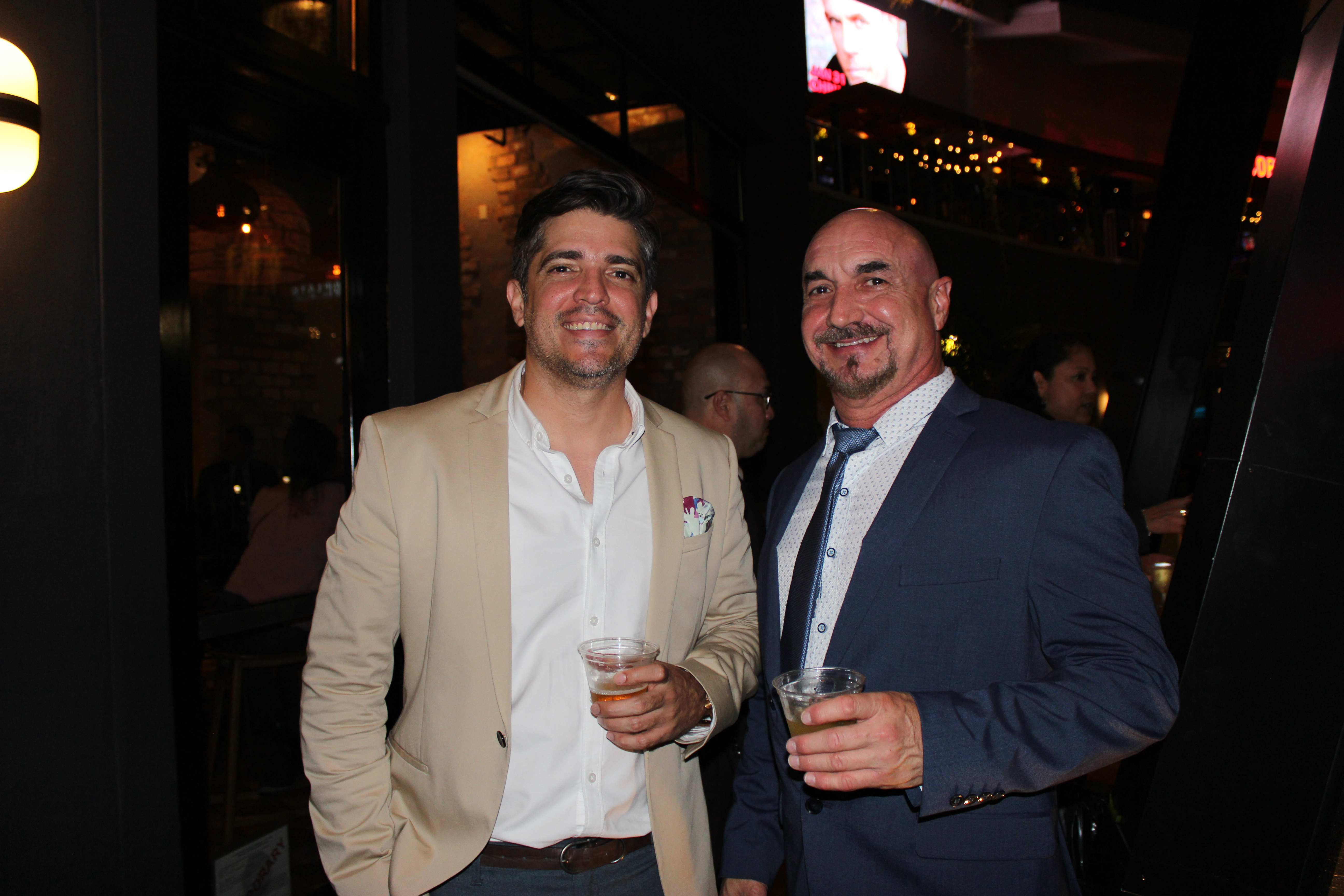Doral Chamber of Commerce introduces Novecento Grand Opening Event, 2 people taking a photo together.