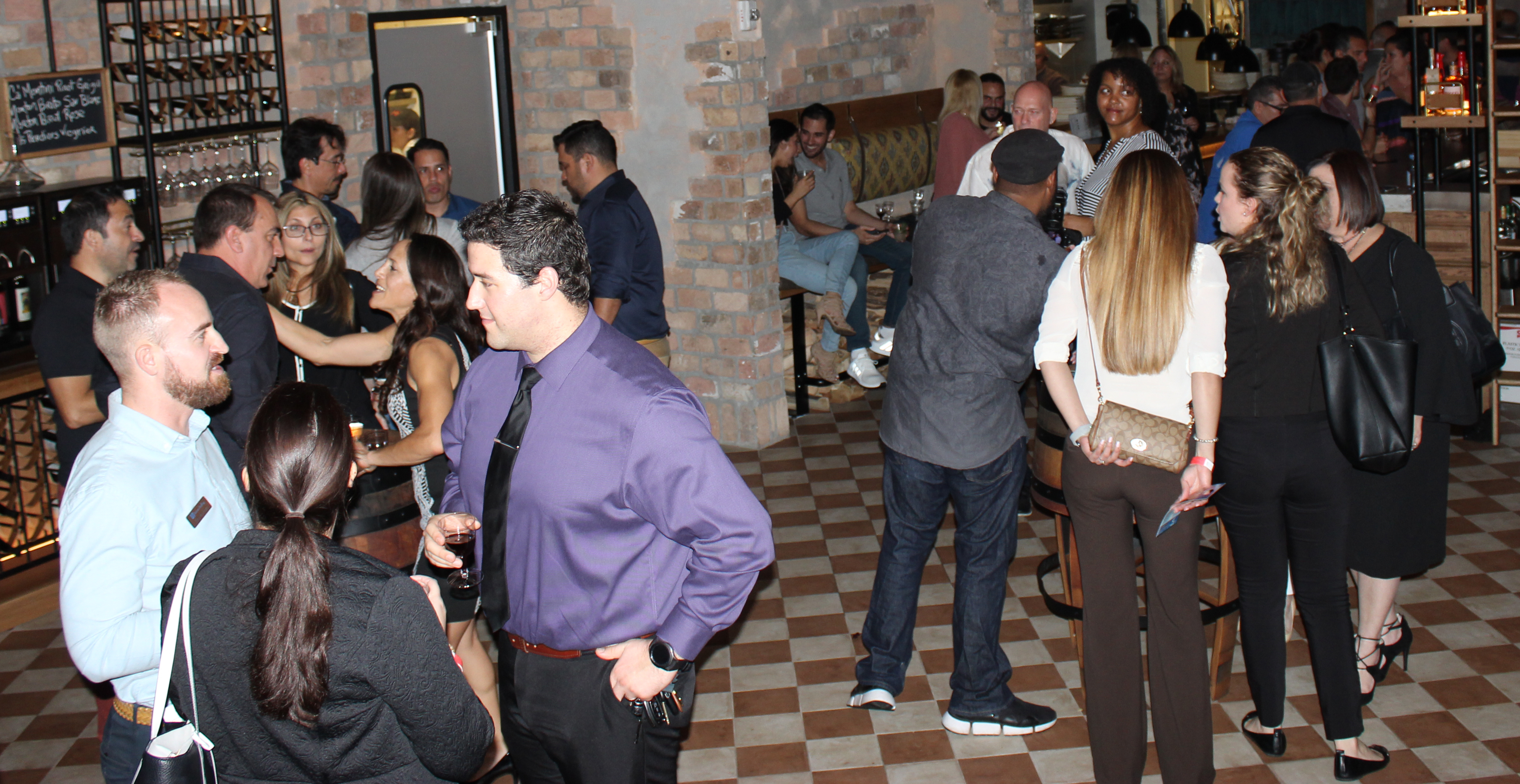 Doral Chamber of Commerce introduces Novecento Grand Opening, groups of people talking and having fun.