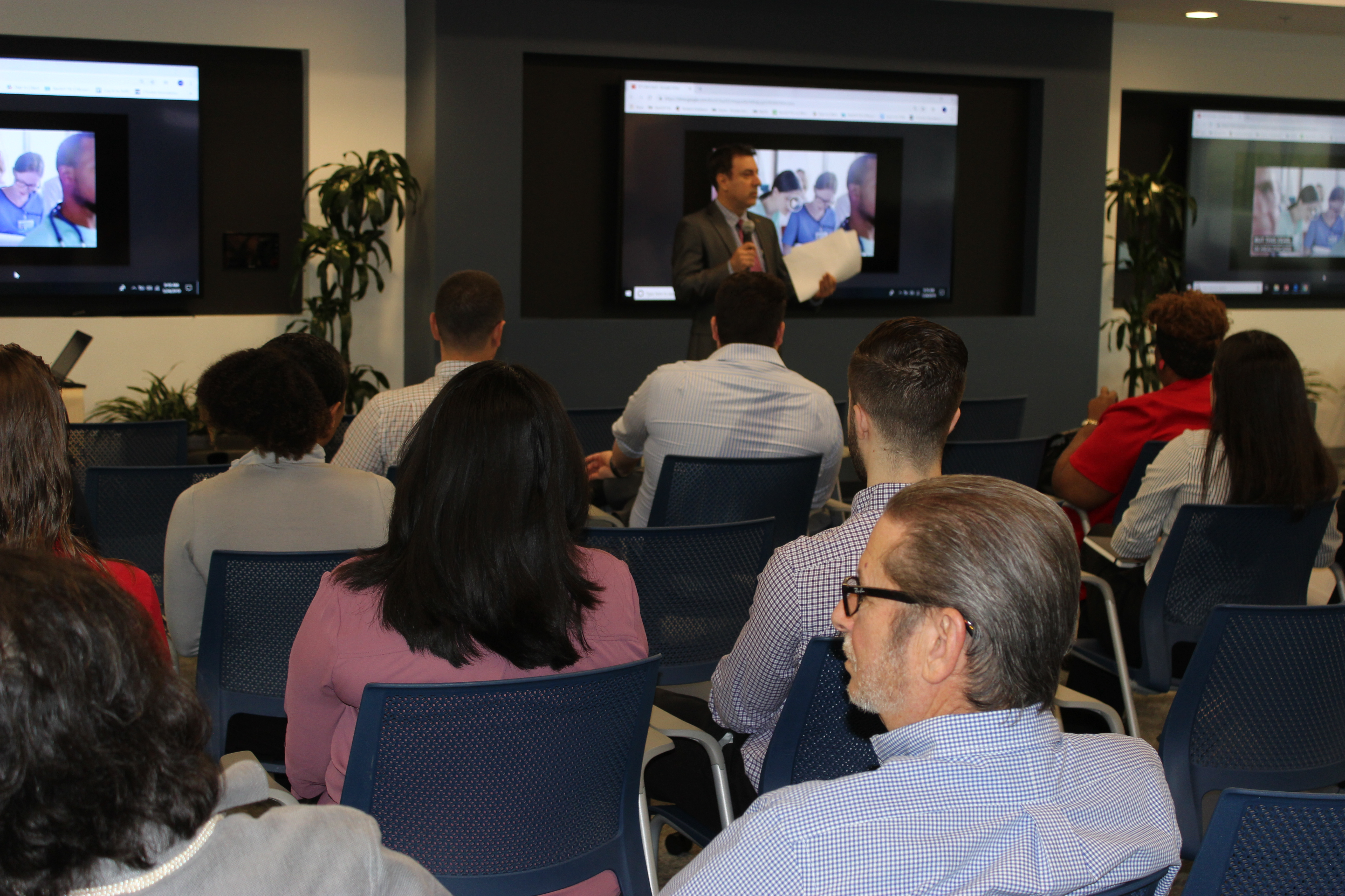 Doral Chamber of Commerce introduces DCC 21st Century Technology event, host explaining to people about technology.