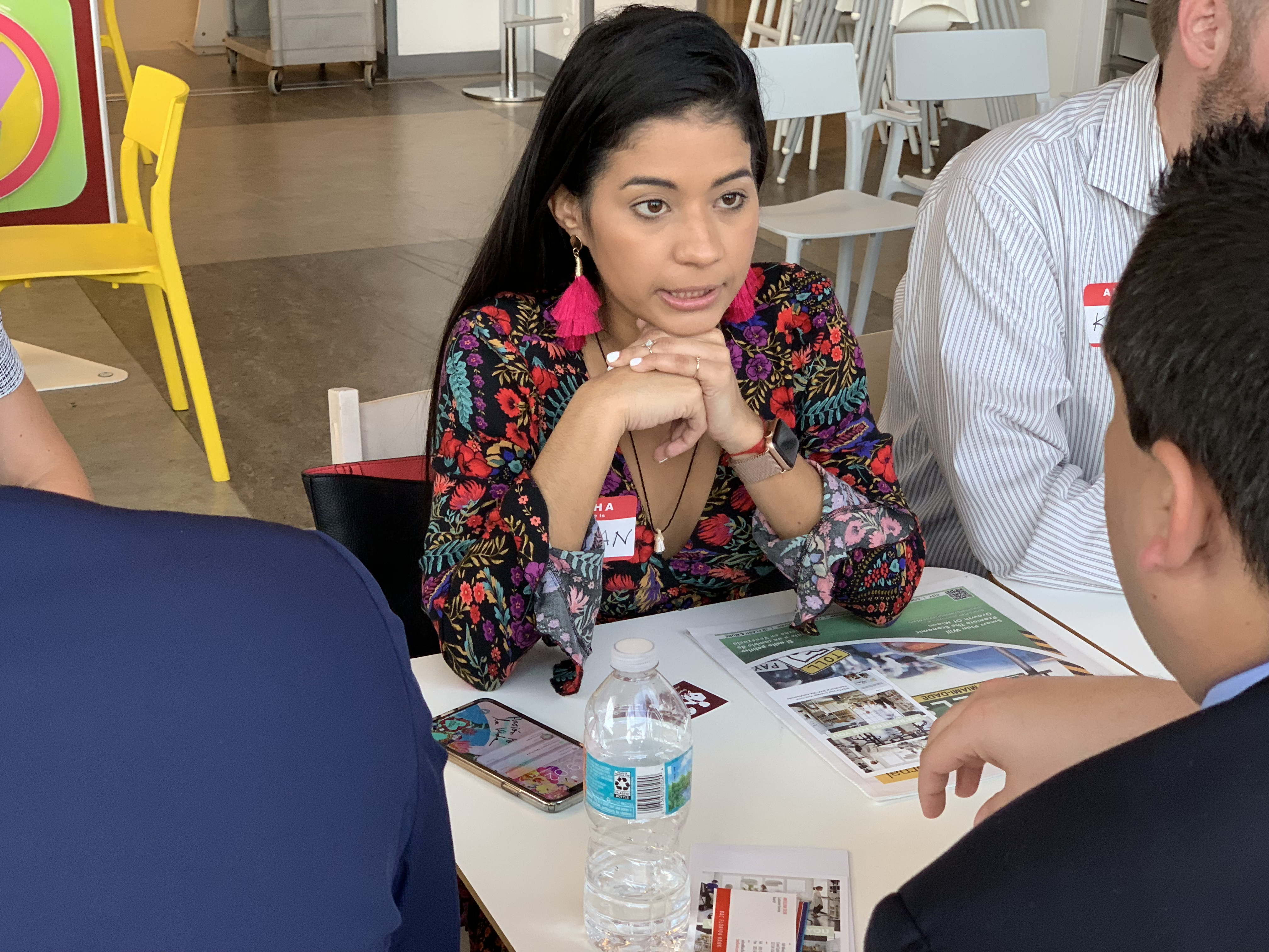 Doral Chamber of Commerce IKEA Speed Networking Event, two members passing cards, taking notes, and marketing each others business.