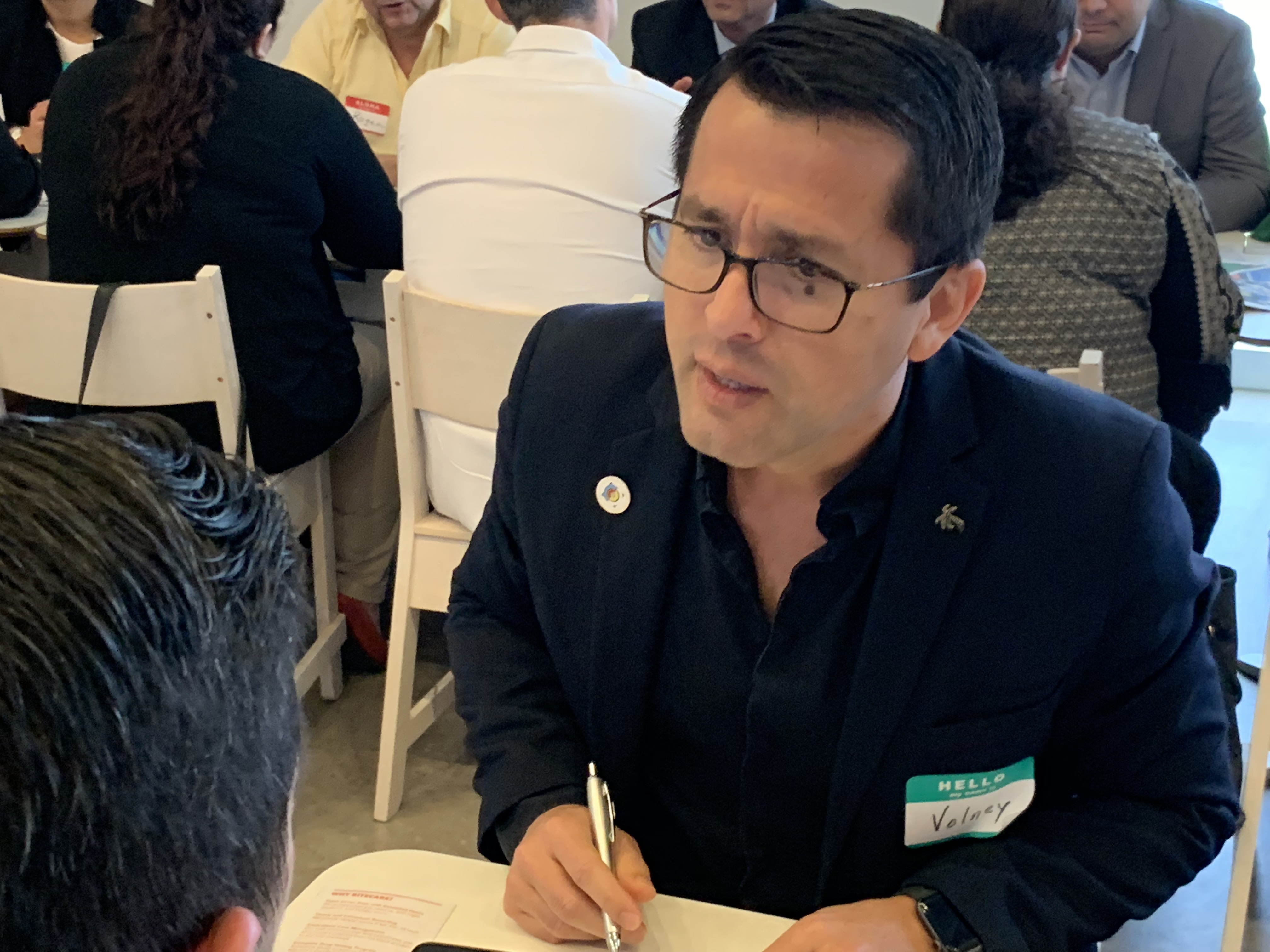 Doral Chamber of Commerce IKEA Speed Networking Event, DCC Member taking notes and writing down info about the other members company.