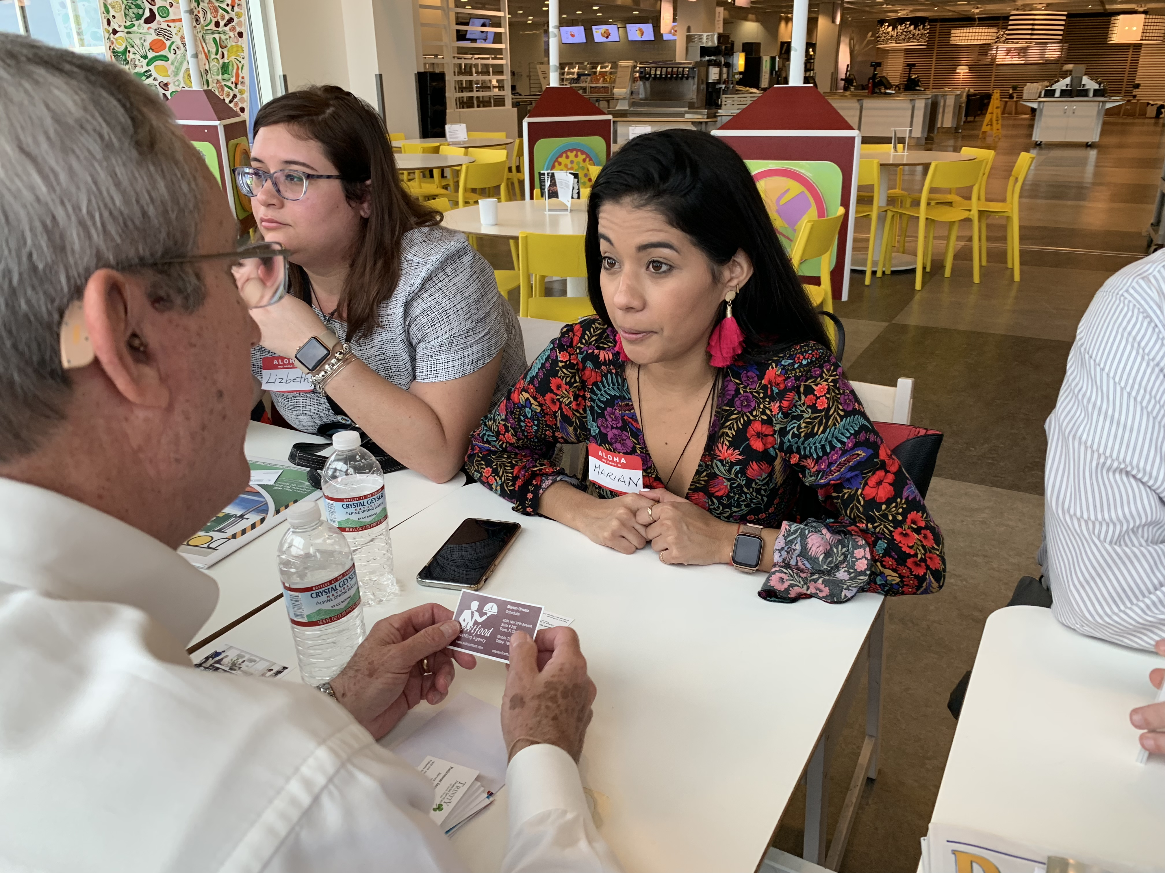 Doral Chamber of Commerce IKEA Speed Networking Event, member passing cards with another member and talking about business.