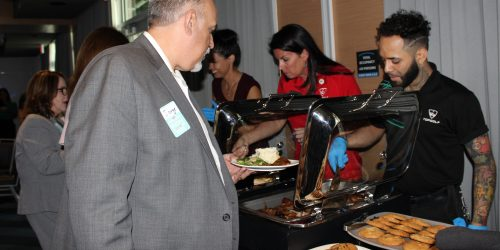 Doral Chamber of Commerce introduces members picking out food from the table at Topgolf Doral Networking Luncheon Event.